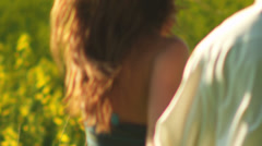 Stock Video Footage of A young couple in love hug and spin around in a open field with yellow flowers