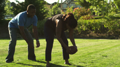 A father plays football with his family, and throws a pass to his son. Stock Footage