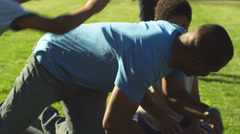 A father plays football with his family, and wrestles with them on the grass Stock Footage