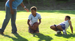 A father plays football with his family, brushes off grass from his son's head - stock footage