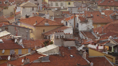 Wide shot of birds flying over Italian rooftops / Nice, France Stock Footage