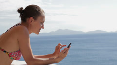 Young woman using cellphone outdoors over blue sea water HD Stock Footage