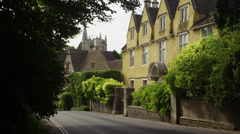 Medium shot of road and large residential house in town / Castle Combe, England, Stock Footage