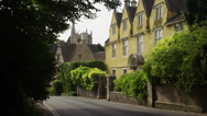 Stock Video Footage of Medium shot of road and large residential house in town / Castle Combe, England,