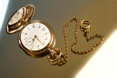 gold pocket watch on gold glass background - stock photo