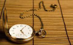 gold pocket watch on bamboo rugs - stock photo