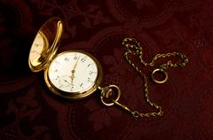 gold pocket watch on maroon cloth - stock photo