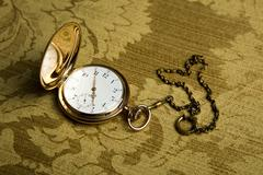 gold pocket watch on gold cloth - stock photo