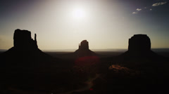 Wide shot of silhouetted rock formation in Monument Valley / Monument Valley, - stock footage