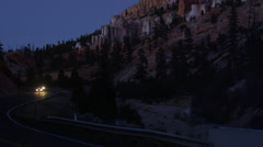 Panning shot of two cars driving on remote road at night in Bryce Canyon / Bryce Stock Footage