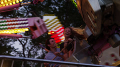 Tracking shot, medium shot of young couple on amusement park ride / American Stock Footage