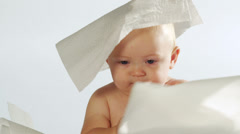 An adorable boy makes funny looks with a paper towel on his head. Stock Footage