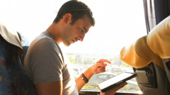 A young man looks through his tablet as he takes a bus ride. Stock Footage