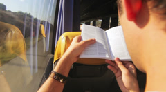 Over the shoulder shot of a young man reading a book as he takes a bus ride. Stock Footage