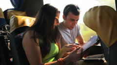 A young couple read a book as they take a bus ride Stock Footage