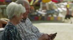 Medium shot of senior couple using cell phone at carnival / American Fork, Utah, Stock Footage