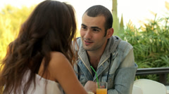 A young couple sitting outside having a drink Stock Footage