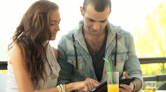 A young couple sitting outside having a drink and using a tablet Stock Footage