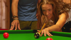 A close up shot of a young woman hitting a cue ball on a green billiards table Stock Footage