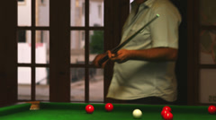 A close up shot of a man hitting a cue ball on a green billiards table Stock Footage