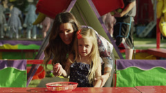 Medium shot of mother helping daughter play game at carnival / American Fork, - stock footage