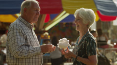 Medium shot of senior couple feeding each other cotton candy at carnival / Stock Footage