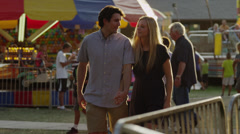 Medium shot to close up of young couple walking at carnival / American Fork, Stock Footage