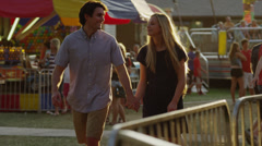 Medium shot to close up of young couple kissing and walking at carnival / Stock Footage