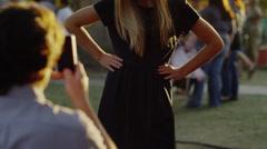 Medium shot of man photographing girlfriend at carnival / American Fork, Utah, Stock Footage