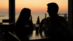 A couple having a drink at sunset Stock Footage