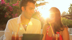 A young couple sitting outside using a tablet during magic hour Stock Footage