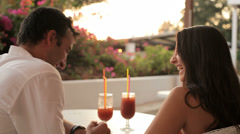 A young couple sitting outside having a drink during magic hour Stock Footage