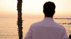 A shot from behind of a young man standing and watching the sunset Stock Footage