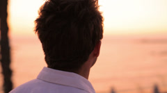 A closeup from behind of a young man standing and watching the sunset Stock Footage