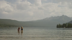 Wide shot of young women running and splashing in lake / Redfish Lake, Idaho, - stock footage