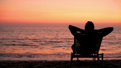 A young man on the beach lying in lawn chair watching the sunset Stock Footage