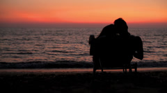 A couple on the beach in a lawn chair embrace each other watching the sunset Stock Footage