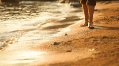 A close up of a young man's feet walking on the beach barefoot during magic hour Stock Footage