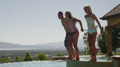 Slow motion, medium shot of girls jumping into swimming pool / Cedar Hills, Stock Footage