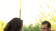 A young couple holding hands sitting outside with drinks Stock Footage