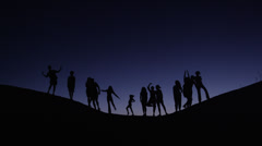 Medium shot of people silhouetted on hill against night sky / Lake Powell, Utah, - stock footage