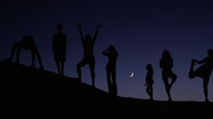 Panning medium shot of people silhouetted on hill against night sky / Lake Stock Footage