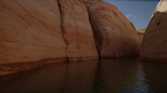 Panning medium shot of rock formation bordering lake / Lake Powell, Utah, United - stock footage