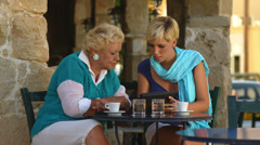 An older woman sits at a table with a younger woman outside looking at a tablet - stock footage