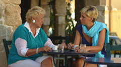 An older woman sits at a table with a younger woman outside talking Stock Footage