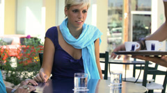 An older woman sits at a table with a younger woman getting served drinks - stock footage