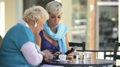 A younger woman sits at a table and shows an older woman how to use a tablet - stock footage