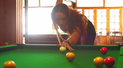 A young woman hitting the cue ball on a green billiard table Stock Footage
