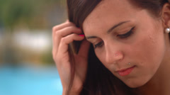 A cute young woman with a flower in her hair sits and looks at a tablet Stock Footage