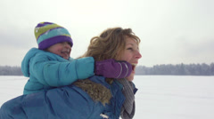 Slow-Mo: Happy Mother Carrying Her Son Piggyback In Snow Stock Footage